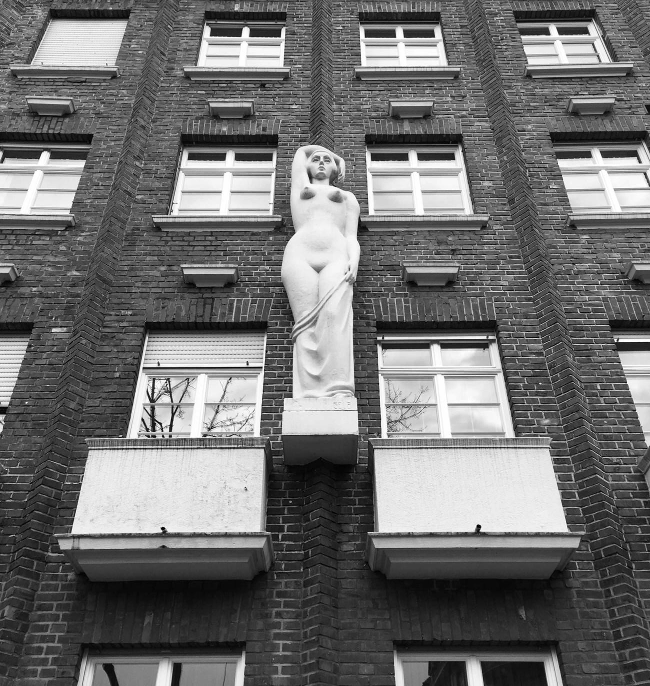 Nackte Frau an der Hauswand